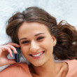 Happy girl socializing on phone - Stock Photo