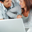 Sweet young couple enjoying themselves with a laptop - Stock Photo