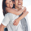 Smiling young couple enjoying piggyback ride - Stock Photo