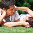 An affectionate young couple relaxing in park - Photo
