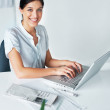 Beautiful young business woman working on laptop - Stock Photo