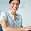Smart young business woman at her desk - Stock Photo