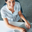 Young female business executive working on laptop in office - Stock Photo