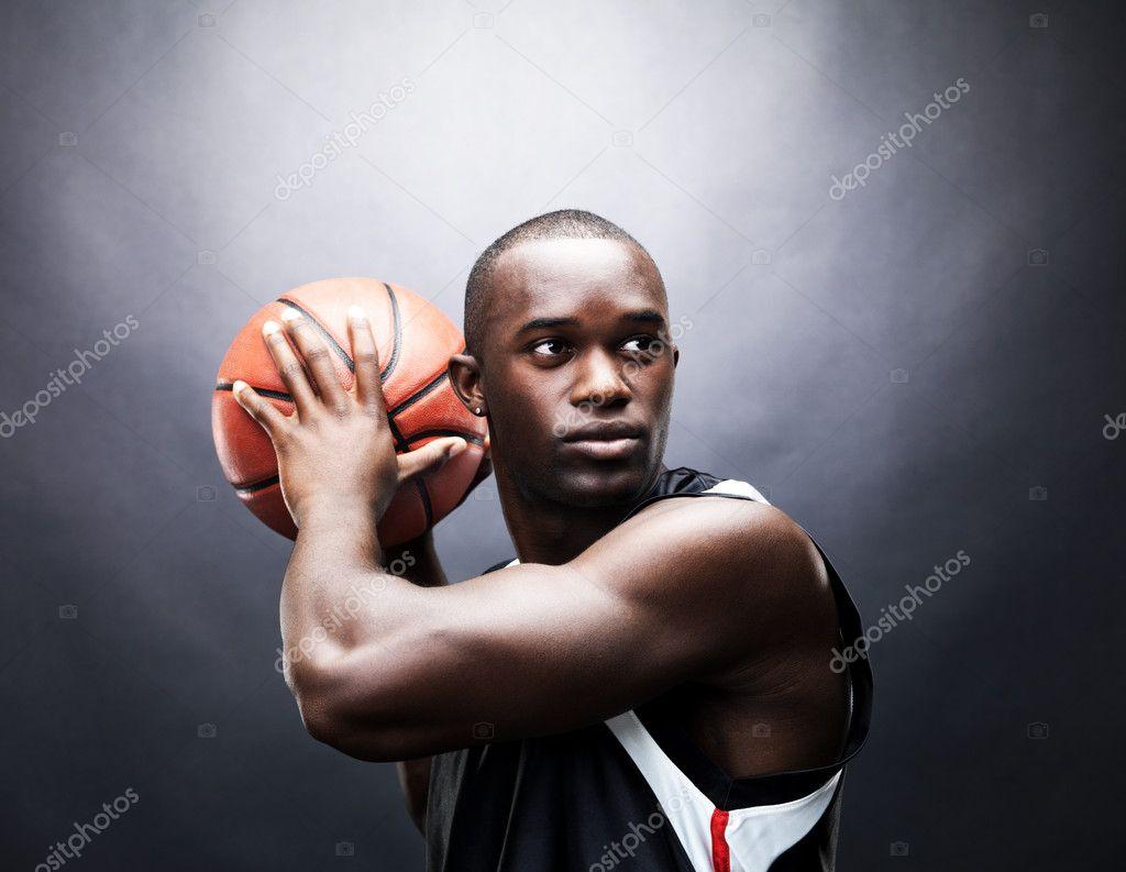 Portrait of a confident young man playing basketball against grunge background  Stock Photo #7759352