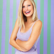 Pretty blond woman smiling with arms crossed - Stock Photo