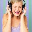 Woman singing while listening to headphones - Stock Photo