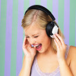 Pretty blonde singing along to music - Stock Photo