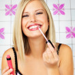 Pretty blond applying lip gloss - Lizenzfreies Foto
