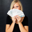 Woman holding fan of money - Stock Photo