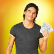Cheerful man holding handful of money - Stock Photo