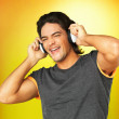 Handsome man singing while listening to music - Stock Photo