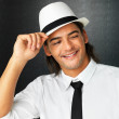 Attractive man in hat winking - Stock Photo
