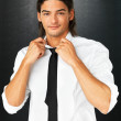 Flirtatious man loosening tie - Stock Photo