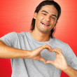Handsome man smiling while making heart sign - Stok fotoğraf