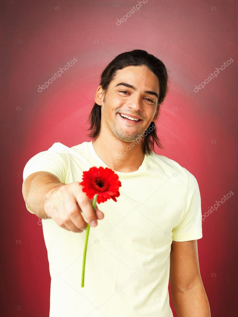 Portrait of happy man holding daisy flower on red background  Stock Photo #7763728
