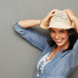 Happy cowgirl holding her hat - Stock Photo