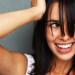 Happy woman with unkept hair looking sideways - Stock Photo