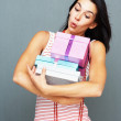 Pretty woman with armful of presents - Stock Photo
