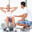 Woman exercising with personal trainer - Stock Photo