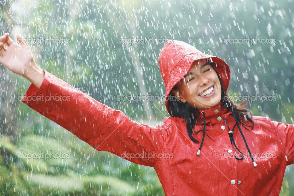 Happy woman in red raincoat smiling as she plays in rain — Stock Photo #7779524