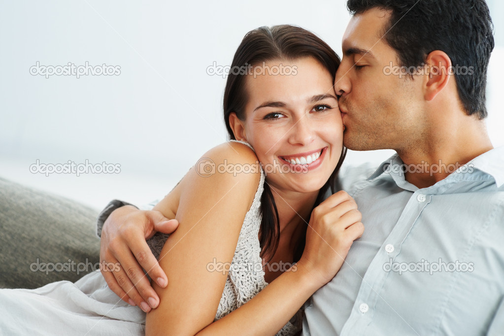 Portrait of smart young man kissing his girlfriend on sofa — Stock Photo #7779990