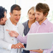 Royalty-Free Stock Photo: Team discussing project while viewing laptop