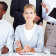 Royalty-Free Stock Photo: Young businesswoman smiling at a meeting with colleagues