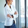 Female executive standing casually while looking out window - Stok fotoğraf