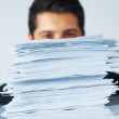 Overworked businessman behind stack of papers - Stock Photo