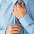 Businessman adjusting tie - Stock Photo