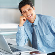 Royalty-Free Stock Photo: Happy executive casually sitting at desk