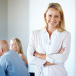 Royalty-Free Stock Photo: Young business woman at a meeting with colleague in background