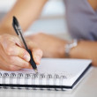 Woman's hand holding a pen taking notes - Stockfoto