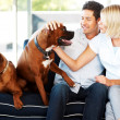 Cute young couple caressing their dog at home - Stock Photo