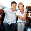 Happy young couple sitting with their pet on couch - Stockfoto