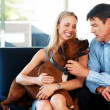 Royalty-Free Stock Photo: Smiling young couple sitting on sofa with pet