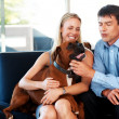 Royalty-Free Stock Photo: Happy couple sitting on couch with a dog