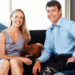 Royalty-Free Stock Photo: Pretty young couple sitting on sofa with their pet dog