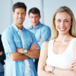 Royalty-Free Stock Photo: Confident young business executive with her team in the backgrou