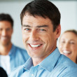 Royalty-Free Stock Photo: Successful business man smiling with his team at the back