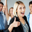 Royalty-Free Stock Photo: Excited businesswoman with thumbs up in fornt of her happy team