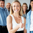 Royalty-Free Stock Photo: Excited businesswoman with success sign and her team in backgrou