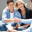 Young couple shaking hand with insurance advisor - Stock Photo