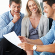 Consultant discussing investment plan with young couple - Stock Photo