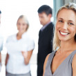 Smiling businesswoman with her colleagues in background - Stockfoto