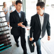 Businesspeople discussing new project while walking - Stock Photo