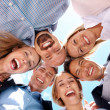 Successful businesspeople standing in huddle - Stock Photo