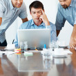 Successful team reviewing proposal on laptop - Stock Photo