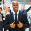 Royalty-Free Stock Photo: Businessman giving his approval with excited colleagues in backg