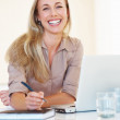 Smiling woman at her desk - Stock Photo
